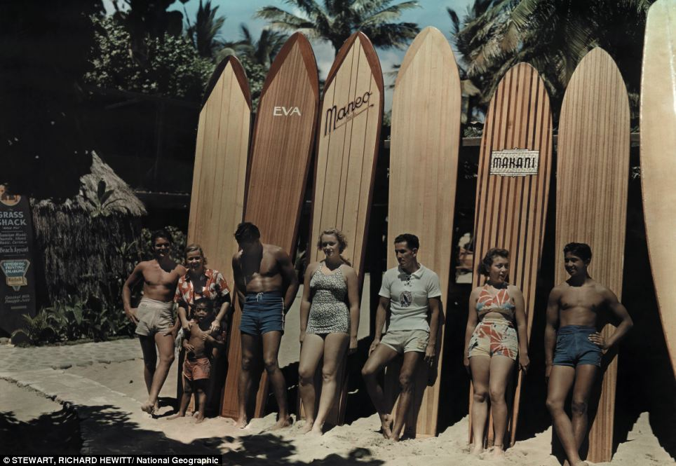 A group of surfers on Waikiki beach in Hawaii pose leaning against their boards