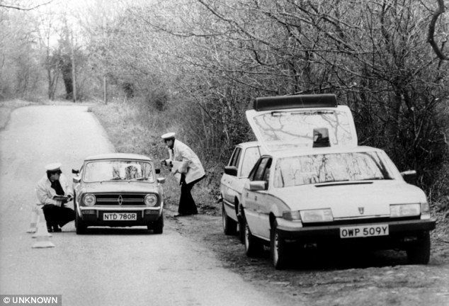 Murder hunt: Police stopping cars near the scene of the murder of Ms Murrell in 1984, near the wood where the elderly woman's body was dumped