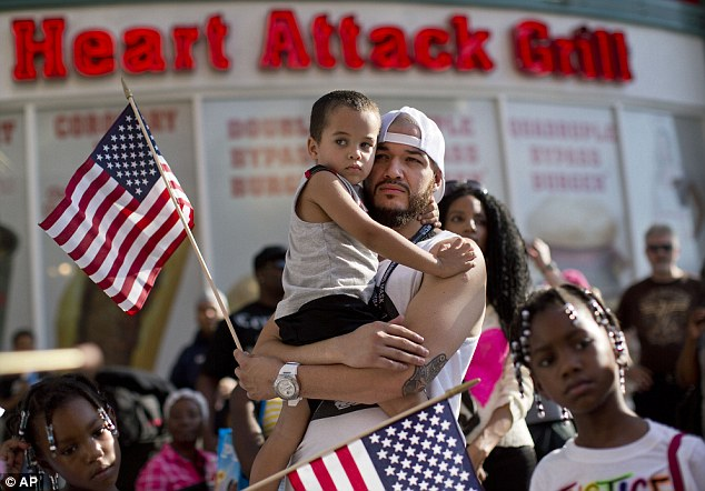 Father and son supporters: Ulysses Diaz, holds his son, Armani Hinton, as they listen to a speech at a rally in Las Vegas.