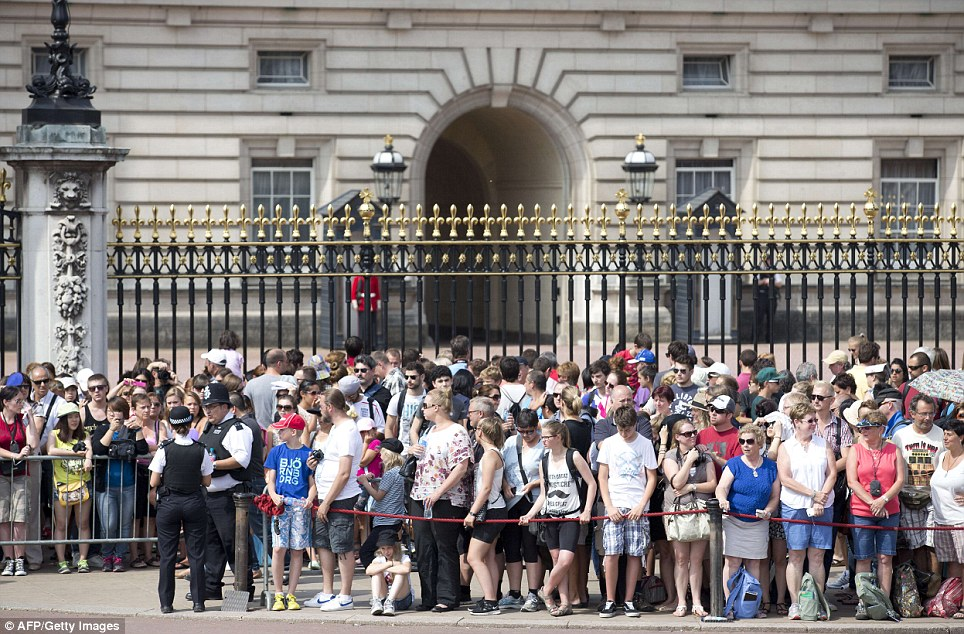 Excited: Huge numbers of people are gathering outside Buckingham Palace, which has had a red rope erected to control crowds