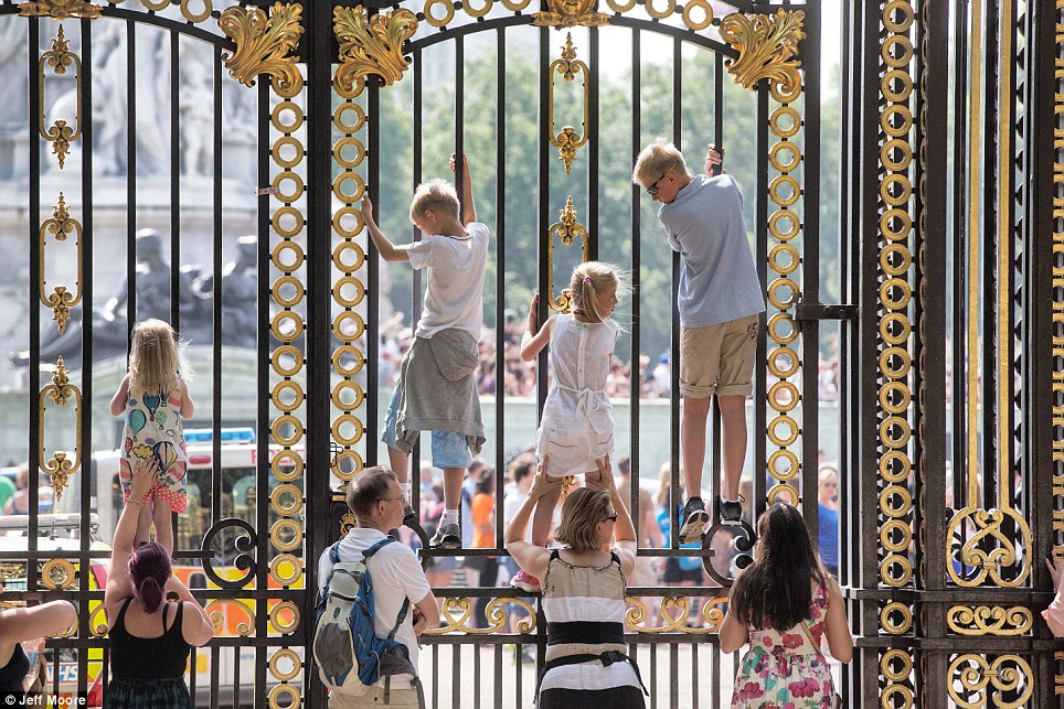 Getting a better view: These excited children climb the gates of the Palace and are among the hundreds getting swept away in the excitement of the royal baby's impending arrival