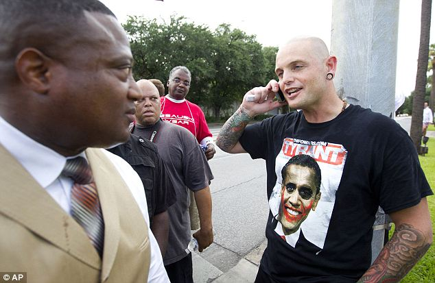 Confrontation: Houston activist Quanell X, left, walks past a man who would not give his name, during a protest in the River Oaks community in Houston on Sunday