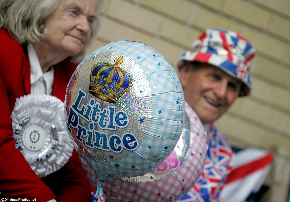 Little prince - or princess? Royal supporters have both balloons with them as they wait outside the hospital ahead of the birth