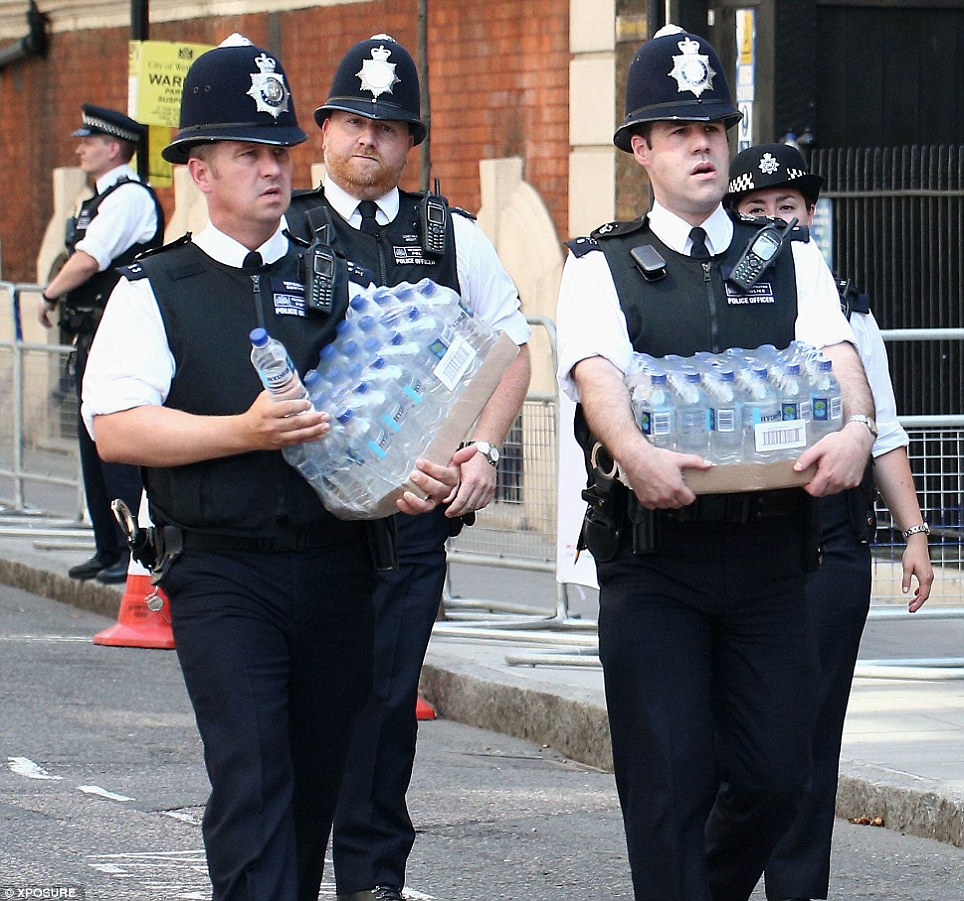 Hot weather: Police officers carry bottles of water outside St Mary's Hospital this afternoon as the heatwave continues