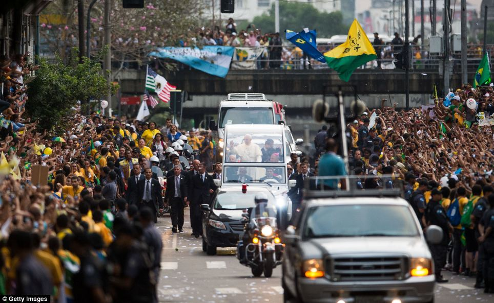 Mobbed: Pope Francis waves to the crowd as he leaves the Metropolitan Cathedral in the Popemobile after arriving in Rio on Monday