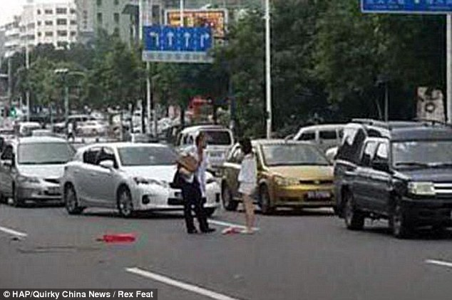 Feeling the heat: The couple were seen arguing in the middle of the street in Dongguan, Guangdong Province, China