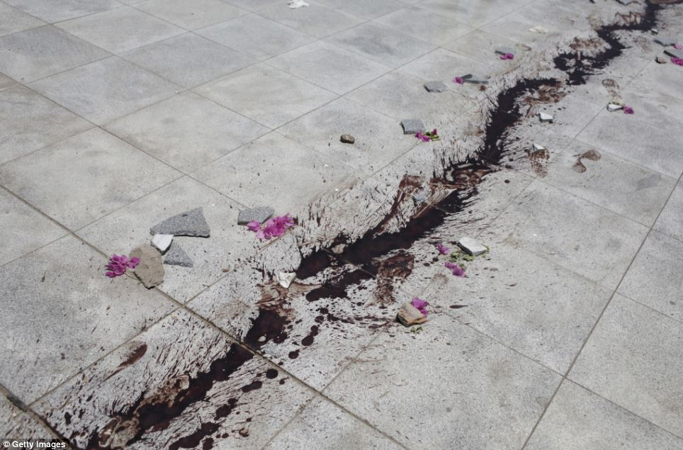 Destruction: Stones and flowers are laid next to a trail of blood that has splattered across a tiled floor during the clashes in the early hours of this morning