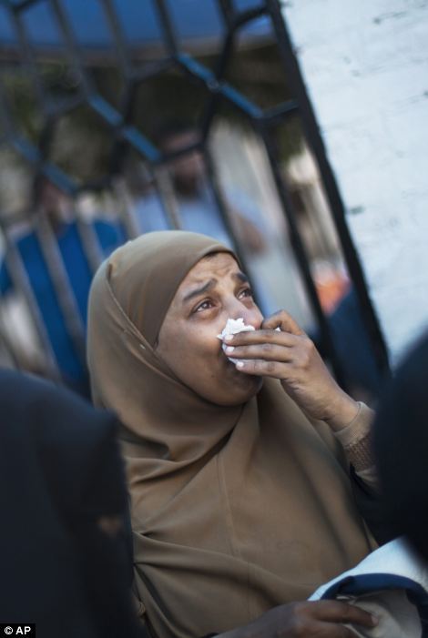A woman cries outside a field hospital in the Nasr area of Cairo where more than 100 people have been killed
