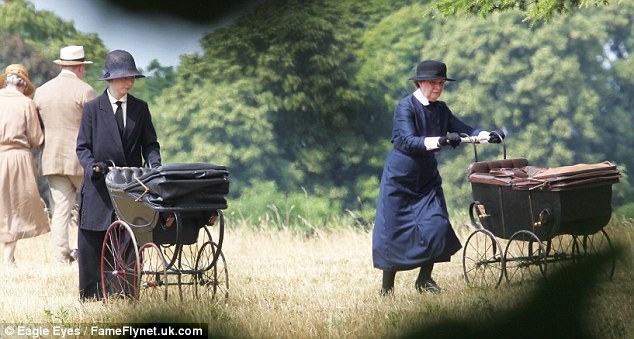 Perambulator: Two extras push some old-fashioned buggies across a field