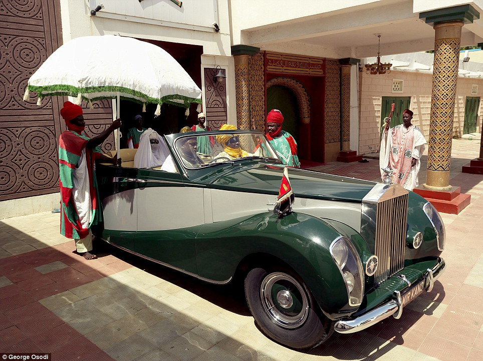 The Emir of Kano is attended by aides as he sits on the back of his vintage Rolls Royce on his way to the Central Mosque in Kano