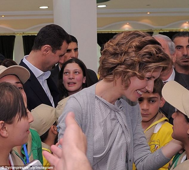Supporting her husband: Asma Assad and her husband grin broadly at another meet and greet, with grim-faced minders conspicuously in the background