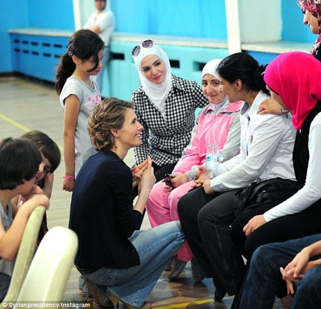 I'm on your level... Mrs Assad meets schoolgirls with their teacher in what appears to be a school gym