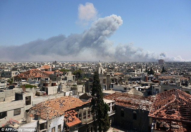 Smoke billows from the ammunition depot following the blast in the Wadi al-Zahab district of Homs