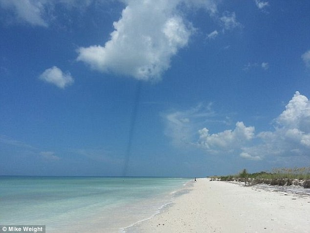 Unsolved: Mike Weight, 73, observed this odd dark line shooting down from a cloud at Honeymoon Island, Florida
