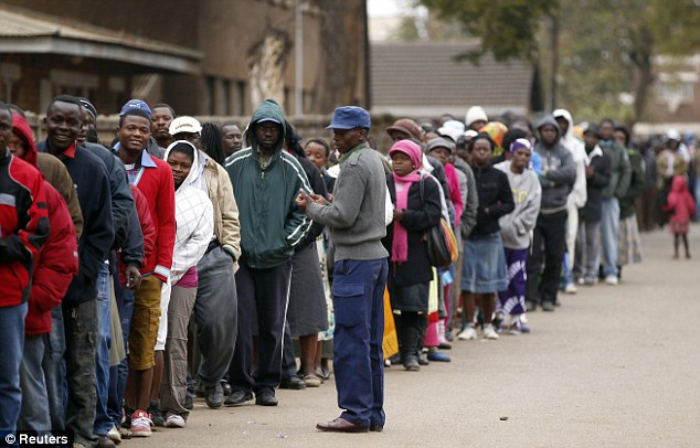 A police officer keeps watch as Zimbabweans waited to cast their vote in Mbare township outside Harare
