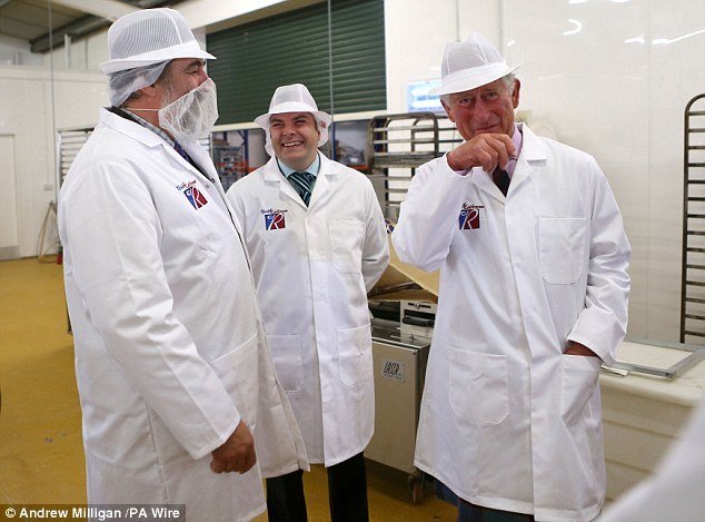 The Prince of Wales with baker Gary Reid (centre) laughs at Viscount Thurso in his beard mask during a visit to Reids bakery