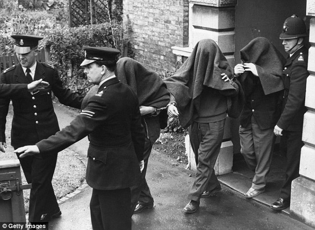 Success: The investigation led to 12 of the robbers being caught and jailed for their role in the crime. Here three of the suspects are pictured being led away from Linslade Court with blankets over their heads