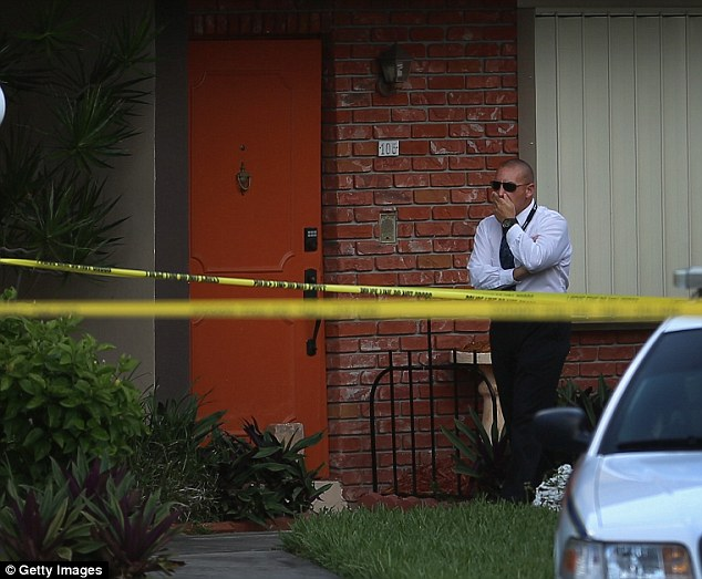A police detective stands near the orange door which is the front door to a townhouse where a husband reportedly confessed on Facebook to murdering his wife