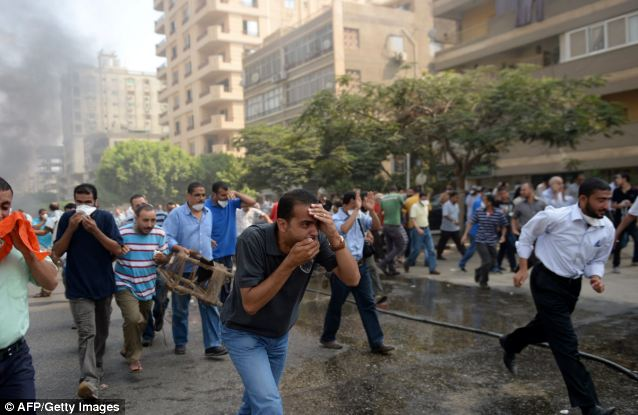 Panic: Egyptian Muslim Brotherhood supporters run for cover from tear gas fired by police in a street leading to Rabaa al-Adawiya