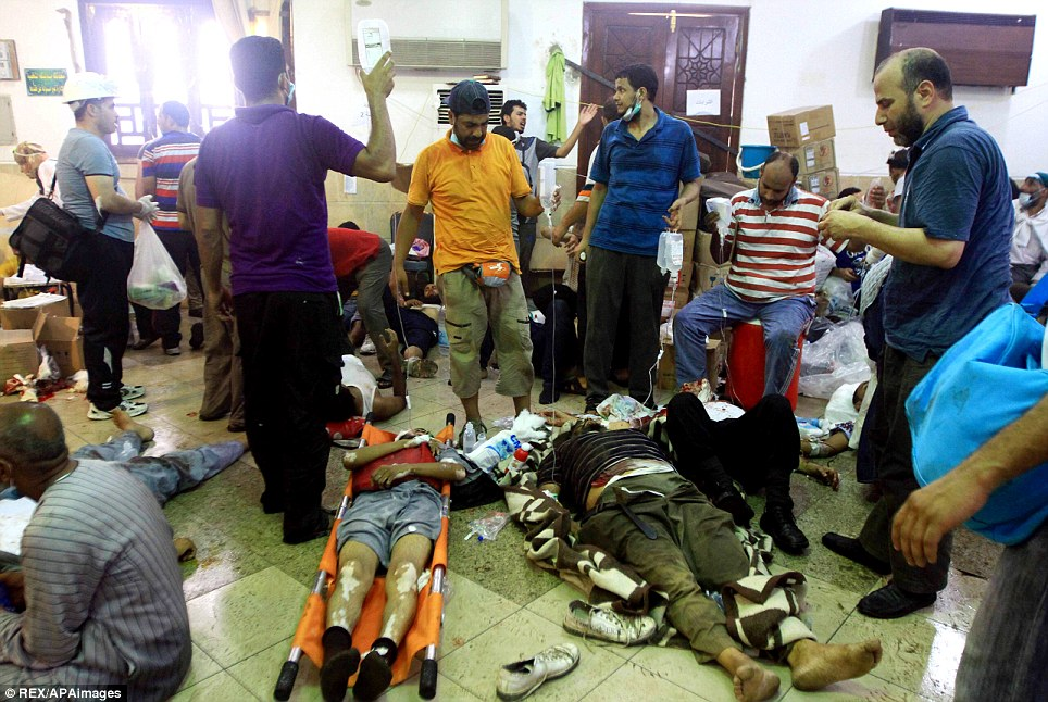 Emergency: Supporters of Morsi treat wounded men in Cairo. Violence spread across much of Egypt after police swept into two encampments of Morsi's supporters