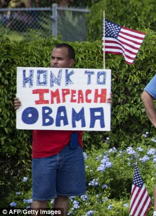 Protesters hold up placards as the president's motorcade passes by in Orlando, Florida on August 10, 2013