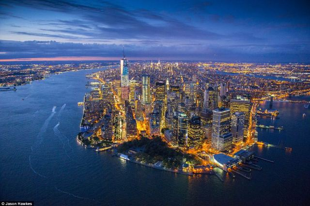 Burning brightly: Aerial photographer Jason Hawkes has caught New York City in action many times of over the years. Here, Manhattan is seen at dusk from its southernmost tip