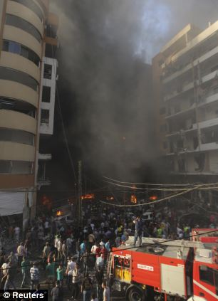People gather around the site of the explosion in Beirut's southern suburbs