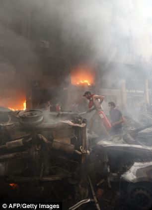 Lebanese emergency services extinguish a flame at the site of a car bomb