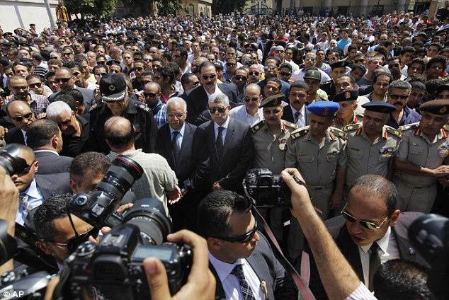 Sadness: Egyptian Interior Minister Mohammed Ibrahim (centre) and top officers of the army and police, march during a military funeral of policemen killed during Wednesday's clashes in Cairo