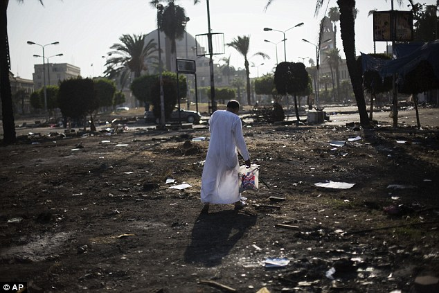Ashes: An Egyptian walks amid charred debris of the Nahda sit-in camp, which was destroyed by security forces