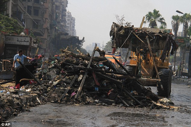 Wreckage: Soldiers clear debris as people sift through it the day after Egyptian security forces clear two encampments of supporters of ousted President Mohammed Morsi in Cairo's Nasr City