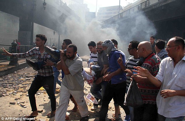 Egyptian Muslim Brotherhood supporters carry a wounded protestor in Cairo's Ramses square