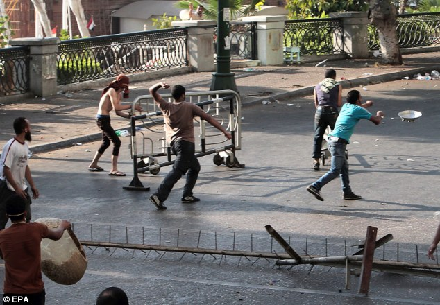Home-made weaponry: Morsi protesters throw rocks, lamps and what appears to be kitchen appliances, near the Four Seasons hotel in Garden City area of Cairo
