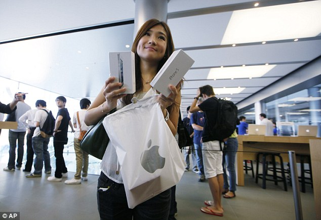 Energy guzzler: A customer shows her new iPhone 5 at the Apple store in Hong Kong