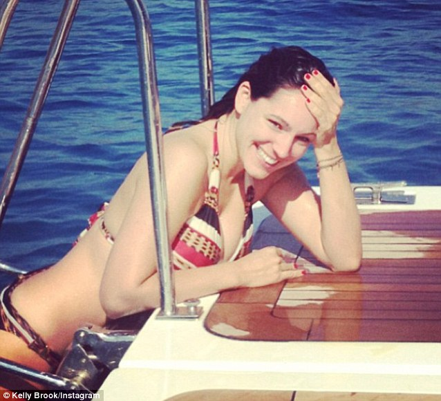Kelly Brook casually drapes herself over the back of a boat - note makeup-free yet dewy complexion