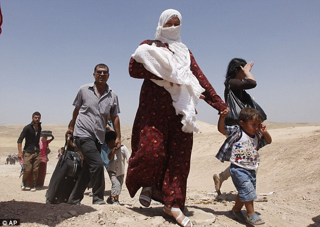 Desperate: Syrian refugees cross into Iraq at the Peshkhabour border point in Dahuk