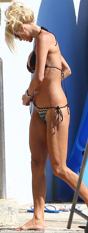 In a twist? The Swedish model re-arranges her bikini bottoms after a refreshing dip in the sea