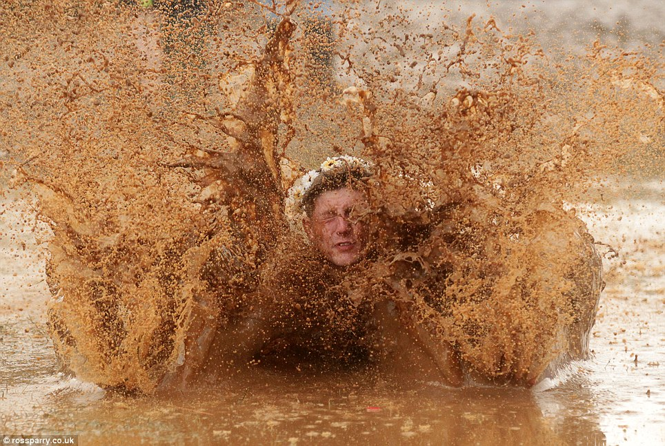 Diving in: A festival goer falls into the mud at Leeds Festival in Bramham Park after heavy rain today