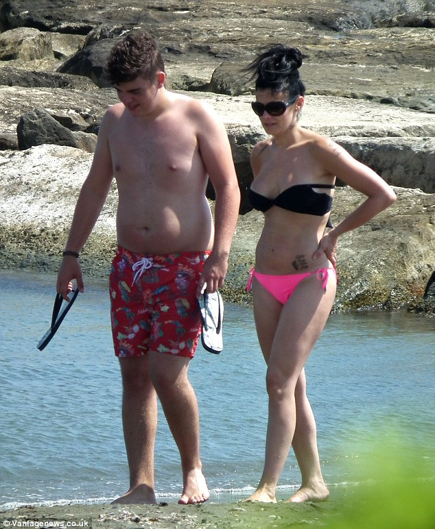 Taking a break: Kym Lomas wandered along the beach with son David on Thursday as she holidayed in Cyprus