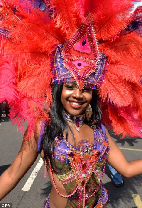 A girls in a giant headdress smiles to the camera as she dances on the street ahead of another troupe