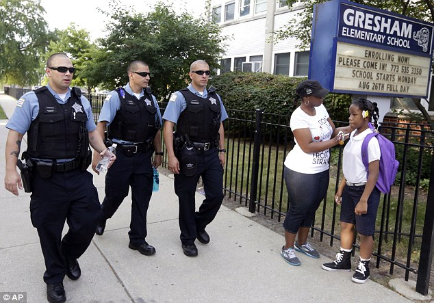 Chicago Police patrol the neighborhood as Crystal Stoval delivers her niece Kayla Porter from their south side home to Gresham Elementary School today
