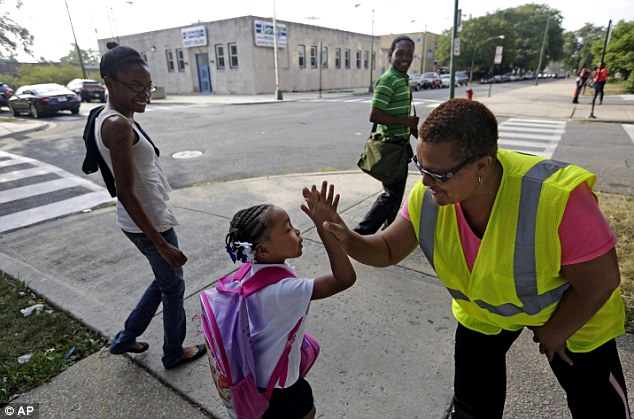 Safety Guard Renee Green high-fives Demari Hill, 5, as she heads to school