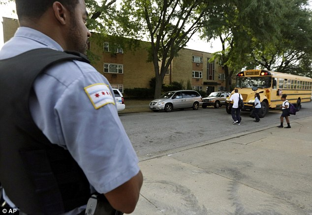 A Chicago Police officer patrolling the neighborhood watches school children board a buss outside Gresham Elementary School