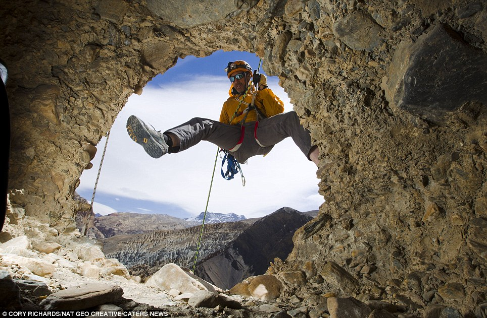 High up: Climber Pete Athans looks inside a cave found near Chuksang. It is not known how people climbed into the caves which are dug into a cliff 155foot above the valley floor