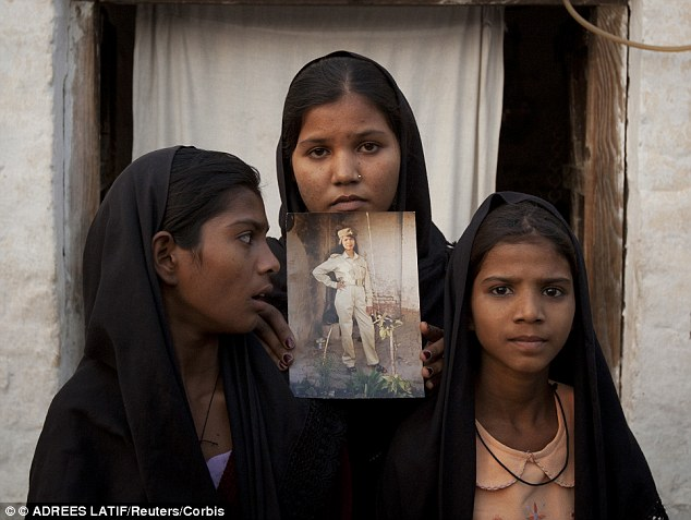 Worried: The daughters of Mrs Bibi pose with an image of their mother