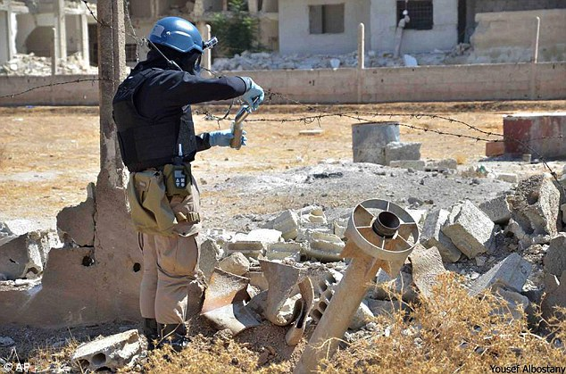 Care: A member of the UN investigation team takes samples of sands near a part of a missile likely to be one of the chemical rockets according to activists, in the Damascus countryside of Ain Terma, Syria