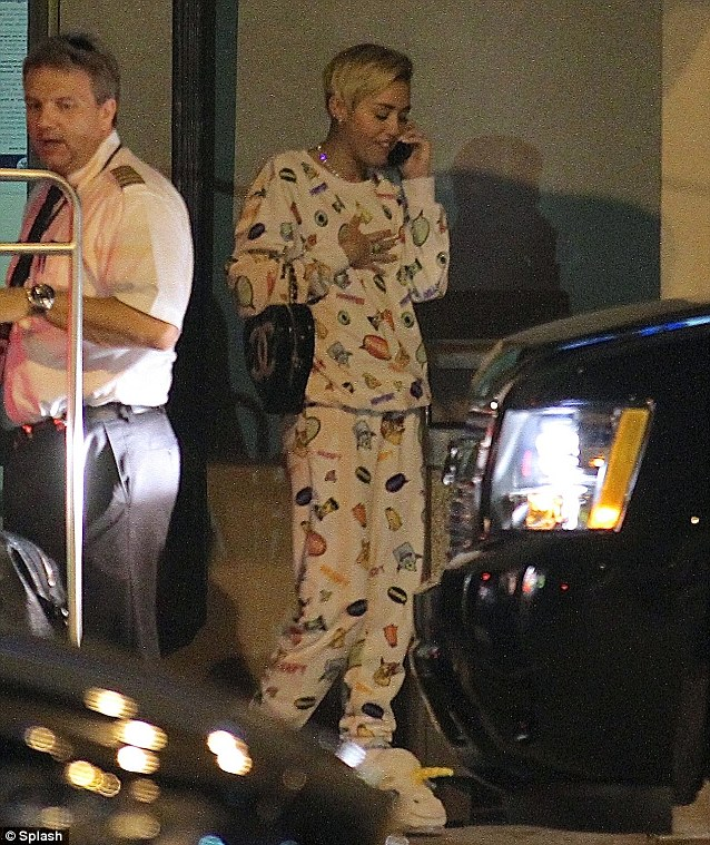 An irregular choice: Miley wears matching food cartoon jumpers and jogging bottoms with unicorn slippers