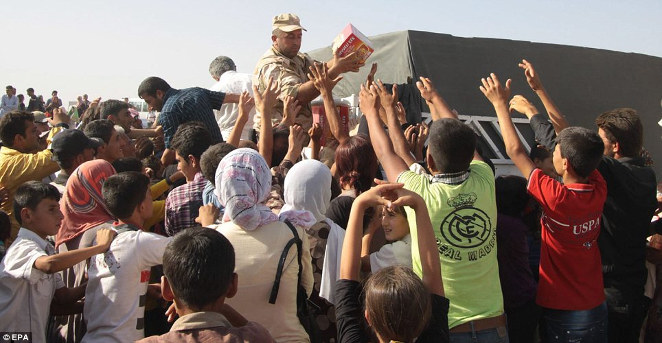 Aid: UN workers hand out supplies to Syrians who have reached the Peshkhabour border crossing between their country and Iraq