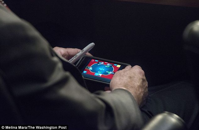 Upping the ante: An eagle-eyed photographer captured a picture of Senator McCain playing poker on his phone during the critical hearing on Tuesday