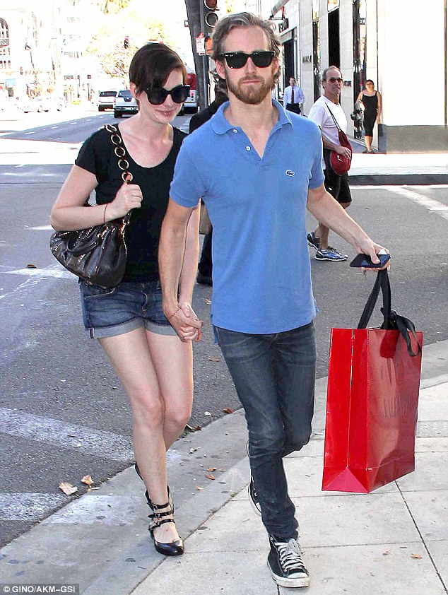 Why so covert: The 30-year-old actress seemed to be hiding behind her husband as they left the store